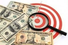 money scattered next to red and white target with a magnifying glass on top